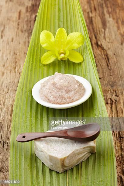 Spa still life with flower, sugar scrub, soap, green leaf