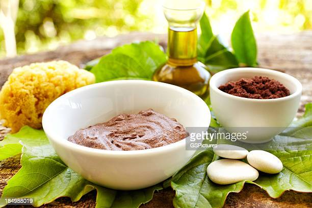 Spa still life with mud mask powder, massage oil outdoors