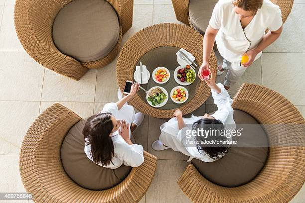 spa therapist serving fresh juice to two middle eastern women - guest stock pictures, royalty-free photos & images