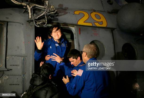 NASA space agency rescue team help Japanese astronaut Norishige Kanai to leave a helicopter prior to a welcome ceremony at the airport of Karaganda...