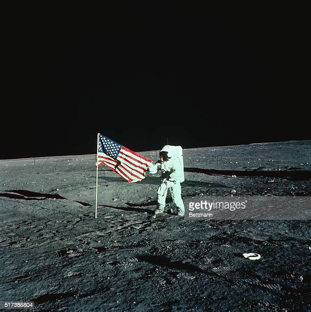 An Apollo 12 astronaut unfurls a plastic United States flag on the moon upon landing November 19th Commander Charles Conrad and lunar module pilot...