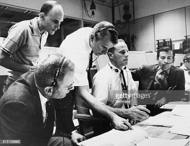 Doinald K Slayton Director Flight Crew Operations and astronauts Thomas K Mattingly and John Young huddle around unidentified fliight controls in...