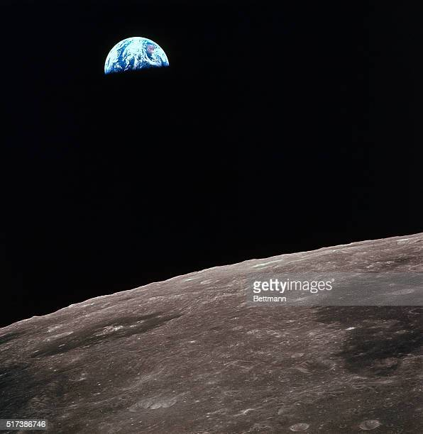 Earthrise over lunar horizon as viewed from command module during Apollo 12 flight The lunar surface as viewed from orbit is part of the back side of...