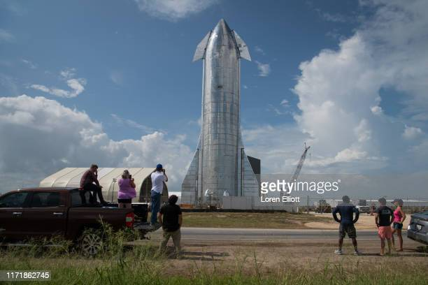 Space enthusiasts look at a prototype of SpaceX's Starship spacecraft at the company's Texas launch facility on September 28 2019 in Boca Chica near...