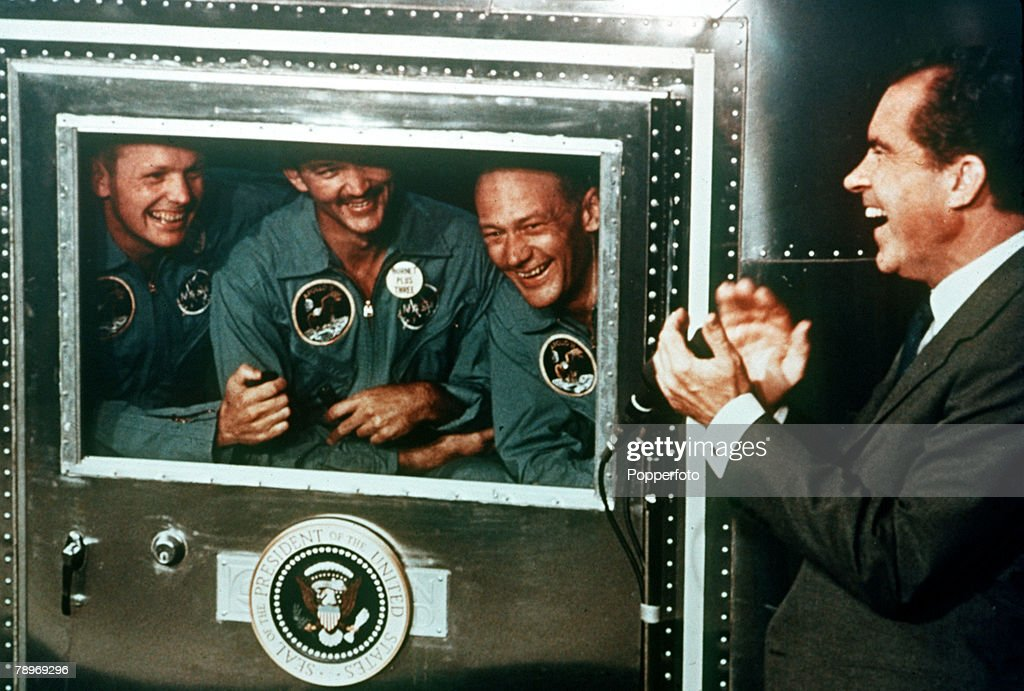 circa 25th July 1969, U,S, President Richard Nixon applauds the Apollo 11 astronauts, l-r, Neil Armstrong, Michael Collins and Buzz Aldrin who are confined in the quarantine trailer, Apollo 11 with it's crew Neil Armstrong, Buzz Aldrin and Michael Collins made history when the lunar module touched down on the moon's surface (July 20th 1969) and Neil Armstrong followed by Buzz Aldrin were the first to walk on the moon