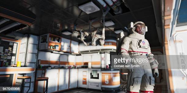 space nightmare: alien creature hanging from ceiling of crew quarters approaches astronaut - space station stock pictures, royalty-free photos & images