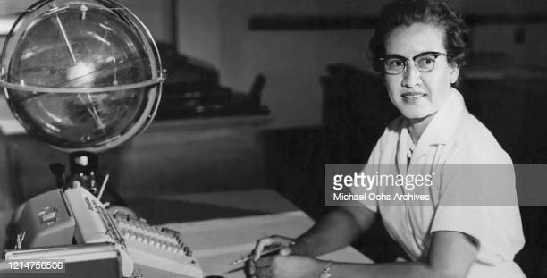 Space scientist, and mathematician Katherine Johnson poses for a portrait at her desk with an adding machine and a 'Celestial Training device' at...