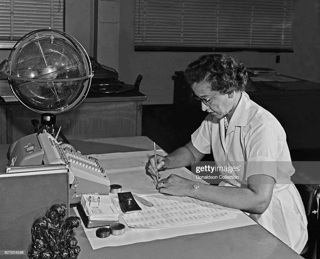 NASA space scientist, and mathematician Katherine Johnson poses for a portrait at her desk with an adding machine and a 'Celestial Training device' at NASA Langley Research Center in 1962 in Hampton, Virginia.