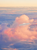 ufo spaceship flying through sunset clouds