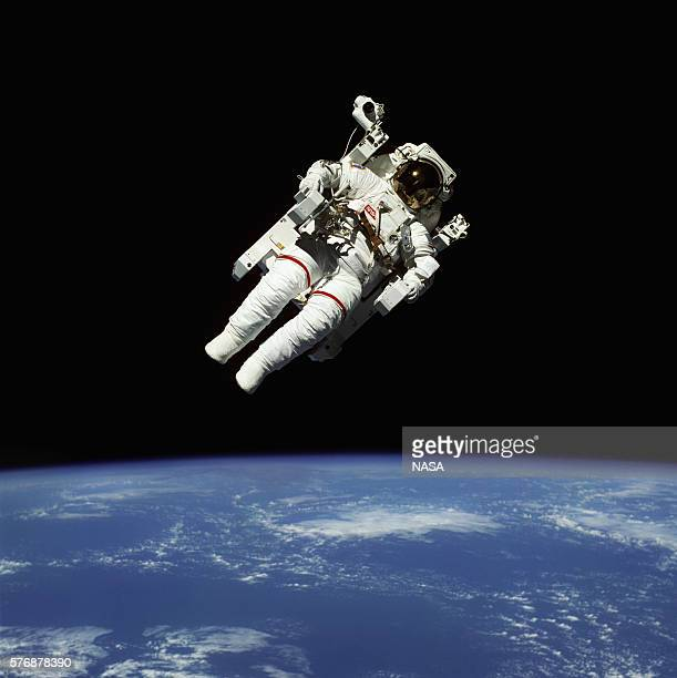 Space shuttle astronaut Bruce McCandless maneuvers through space in a selfcontained suit that allows him to float free of the shuttle craft | View...