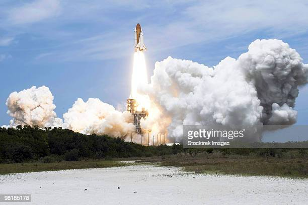 space shuttle atlantis lifts off from its launch pad toward earth orbit. - transbordador espacial fotografías e imágenes de stock
