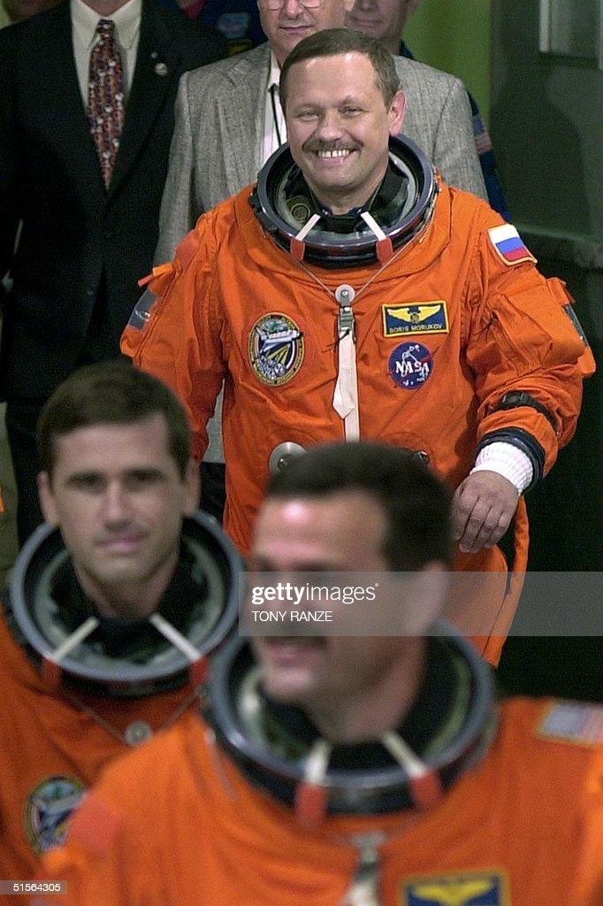 Space shuttle Atlantis Pilot Scott Altman is followed by Russian Mission Specialist Yuri Ivanovich Malenchenko as Russian Mission Specialist Boris Morukov smiles as they depart the Operations and Checkout building and head to launch pad 39-B at the Kennedy Space Center, in Florida, 08 September 2000. Atlantis and her International crew of seven are scheduled to blast off this morning on an 11-day International Space Station mission. AFP PHOTO/Tony RANZE