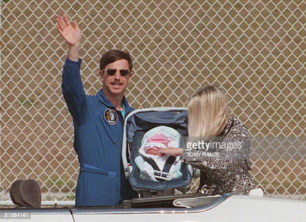 Space Shuttle Columbia Pilot Scott Horowitz waves 21 February showing his tenday old daughter Arielle with his wife Lisa during a visit to Kennedy...