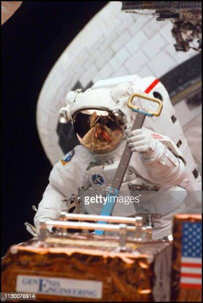 Space Shuttle Discovery Astronaut Mark Lee 16 February moves a piece of equipment in the Shuttle's cargo bay during the third day of spacewalks to...