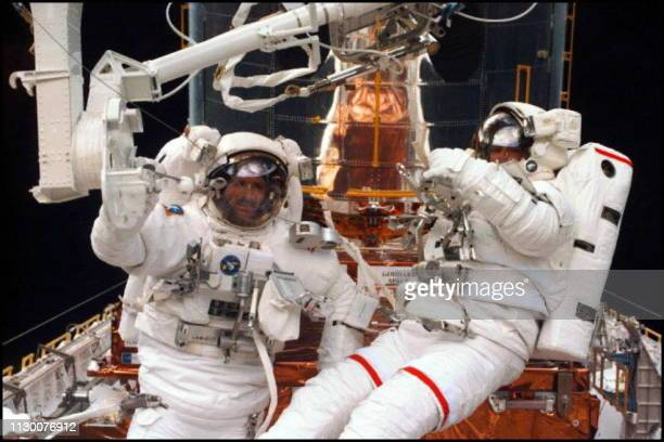 Space Shuttle Discovery Astronauts Steve Smith and Mark Lee 16 February with the Hubble Space Telescope in the backgound in the Shuttle's cargo bay...