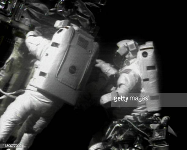 US space shuttle Discovery Mission Specialist Steve Smith of the US and fellow US Mission Specialist John Grunsfeld work on the side of the Hubble...