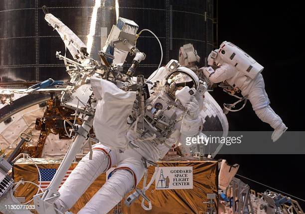 US space shuttle Discovery Mission Specialist Steve Smith of the US prepares to take a photo with a 35mm camera as fellow US Mission Specialist John...