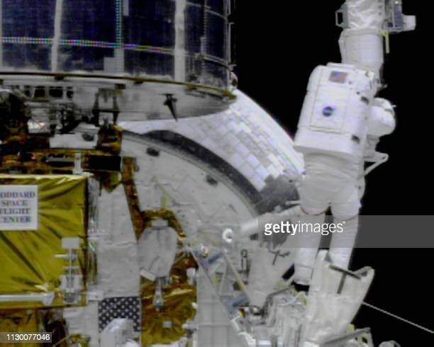 Space shuttle Discovery US Mission Specialist Steve Smith dismantles equipment used in the third and final space walk to service the Hubble Space...