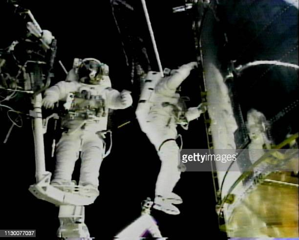 Space shuttle Discovery US Mission Specialist Steve Smith rides the robot arm as US Mission Specialist John Grunsfeld climbs up the side of the...