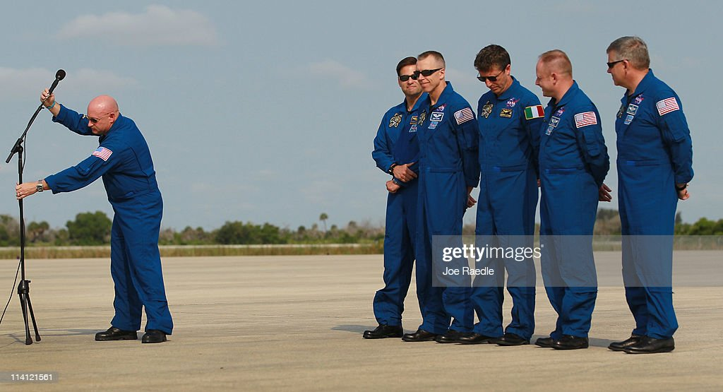 Space shuttle Endeavour commander Mark Kelly (L) moves the microphone after speaking to the media as crew members (L-R) Greg Chamitoff, Andrew Feustel, Roberto Vittori, Michael Fincke and pilot Gregory Johnson stand behind him after their arrival at Kennedy Space Center on May 12, 2011 in Cape Canaveral, Florida. Commander Kelly's wife, congresswoman Gabrielle Giffords, who was shot in the head at a meet-and-greet in her hometown of Tucson, Arizona, plans on attending the launch. Space shuttle Endeavour is scheduled to launch on its final flight to the space station on May 16th.