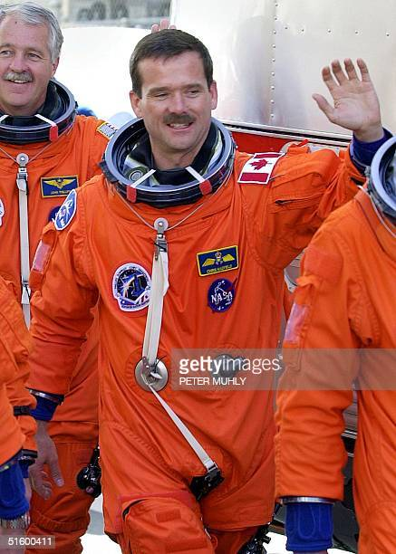 US space shuttle Endeavour crew member Chris Hadfield of the Canadian Space Agency waves as he departs the Operations and Checkout building enroute...