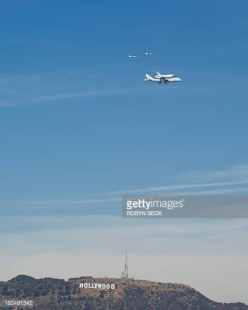 Space Shuttle Endeavour mounted atop NASA's modified Boeing 747 flies over the Hollywood Sign in Hollywood California on its final flight on...