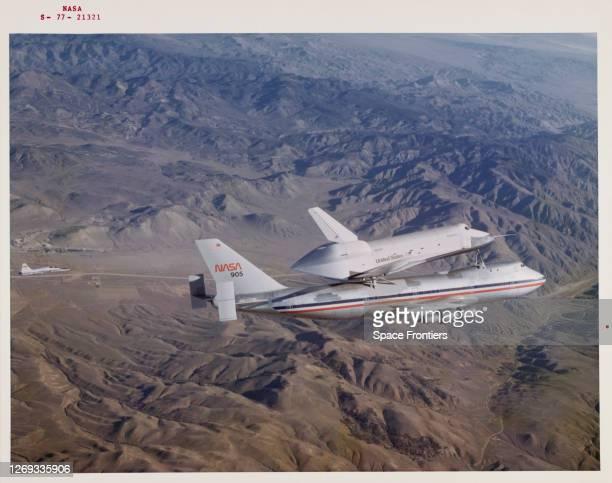 Space Shuttle Enterprise rides piggyback atop NASA 905, a 747 carrier aircraft flies over the desert and mountains of southern California during the...
