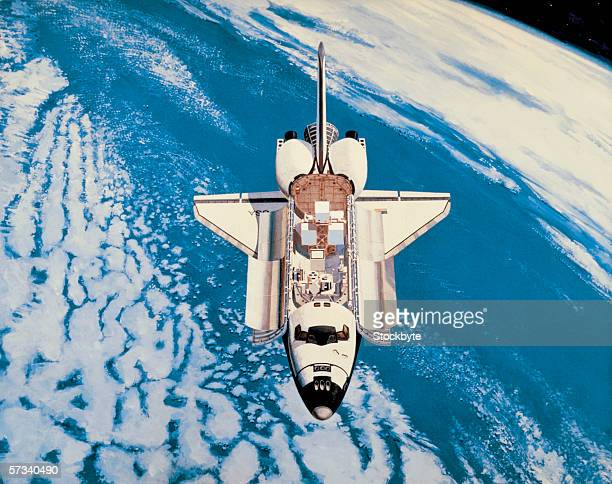 space shuttle in orbit around the earth - space shuttle stock photos and pictures