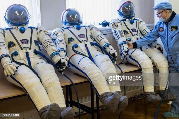 Space suits of Roscosmos cosmonaut Anton Shkaplerov NASA astronaut Scott Tingle and Norishige Kanai of the Japan Aerospace Exploration Agency are...