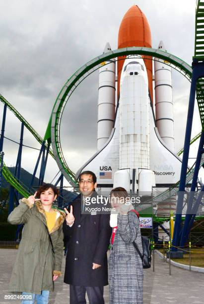 Space World amusement park official Naoyuki Shimada and visitors pose for a photo near a Space Shuttle replica in the southwestern Japan city of...