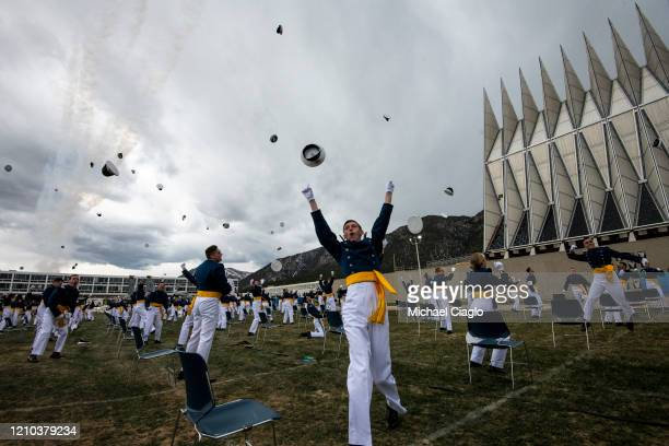 Spaced eight feet apart United States Air Force Academy cadets celebrate their graduation as a team of F16 Air Force Thunderbirds fly over the...
