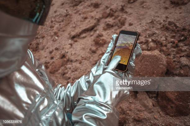 spaceman examining new planet, using smartphone - astronaut stock-fotos und bilder