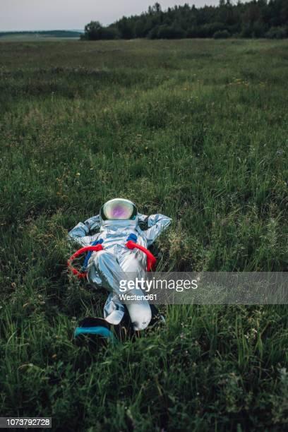 spaceman exploring nature, relaxing in meadow - schutzanzug stock-fotos und bilder