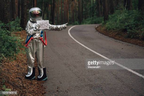 spaceman hitchhiking to mars, standing on road in forest - extraterrestre fotografías e imágenes de stock