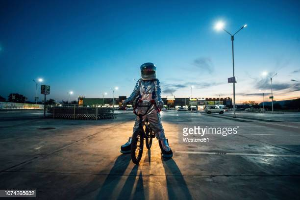 spaceman in the city at night on parking lot with bmx bike - bizarre stock pictures, royalty-free photos & images