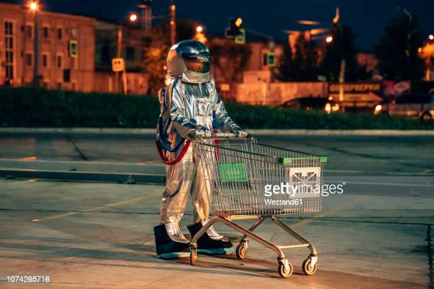 spaceman in the city at night on parking lot with shopping cart - space suit stock pictures, royalty-free photos & images