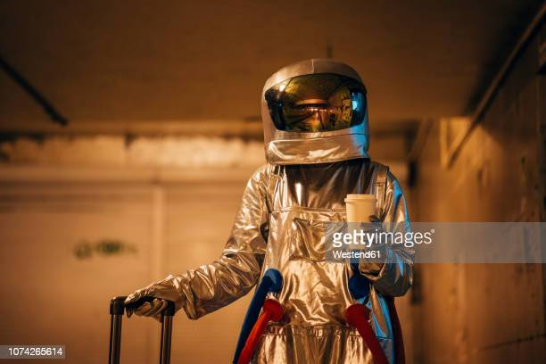 spaceman in the city at night standing in underpass with rolling suitcase and takeaway coffee - space suit stock pictures, royalty-free photos & images