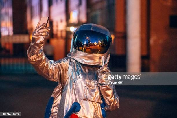 spaceman in the city at night taking a selfie - social media stock-fotos und bilder