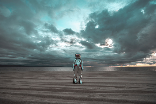 Spaceman standing alone at lake on nameless planet - gettyimageskorea