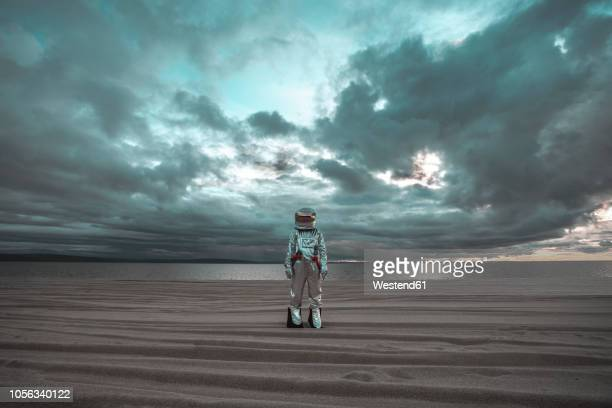 spaceman standing alone at lake on nameless planet - ideas stock-fotos und bilder