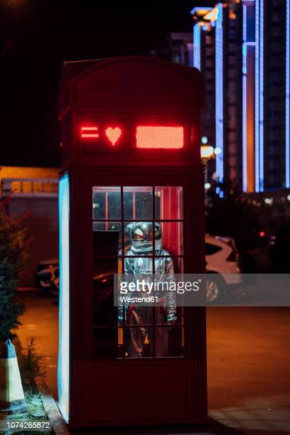 Spaceman standing in a telephone box at night
