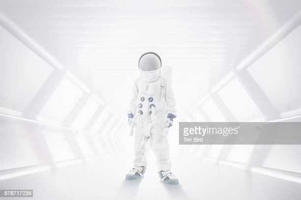 spaceman standing in tunnel - astronaut stock-fotos und bilder