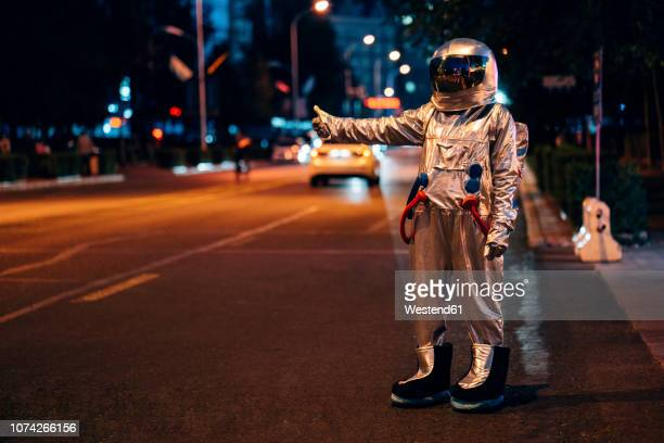 spaceman standing on a street in the city at night hitchhiking - hitchhiking stock pictures, royalty-free photos & images
