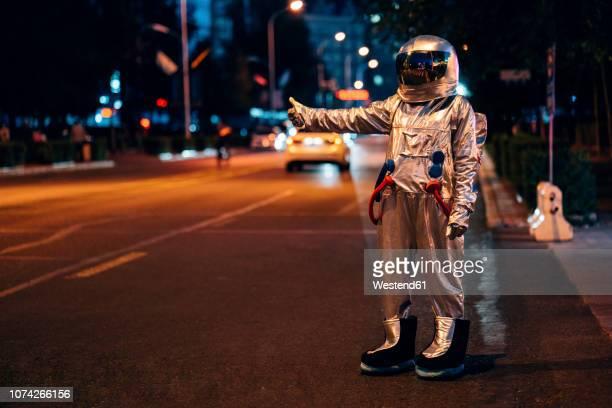 spaceman standing on a street in the city at night hitchhiking - straßenrand stock-fotos und bilder