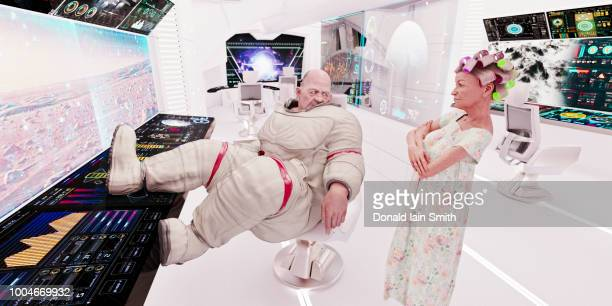 spaceship life: aging overweight astronaut and mature woman with hair curlers in control room of starship - chubby granny fotografías e imágenes de stock