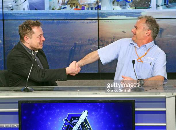 SpaceX CEO Elon Musk left shakes the hand of CTO Martin Halliwell SES Satellites after a SpaceX Falcon 9 rocket powered by a previously flown...