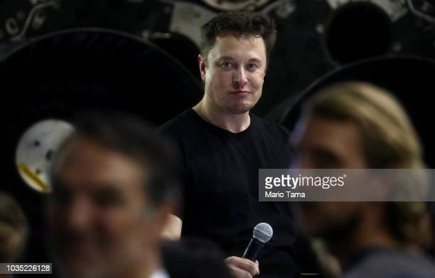 SpaceX CEO Elon Musk listens to a question at a press conference where he announced the Japanese billionaire chosen by the company to fly around the...