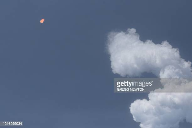 A SpaceX Falcon 9 rocket carrying the Crew Dragon spacecraft breaks away from its contrail shortly after liftoff from launch complex 39A at the...