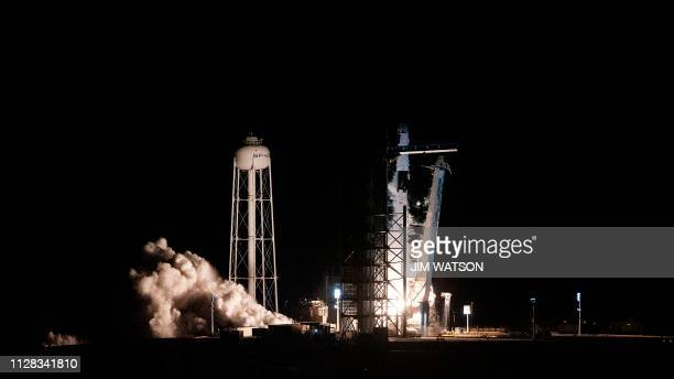 TOPSHOT SpaceX Falcon 9 rocket with the company's Crew Dragon spacecraft onboard takes off during the Demo1 mission at the Kennedy Space Center in...