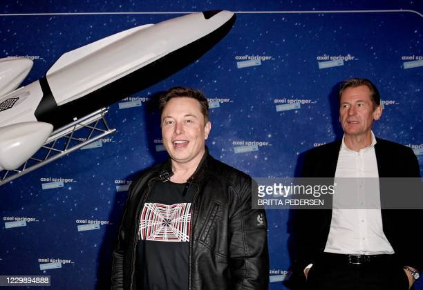 SpaceX owner and Tesla CEO Elon Musk gestures as he arrives on the red carpet next to Axel Springer CEO Mathias Doepfner for the Axel Springer Awards...